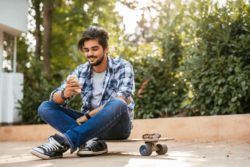 teenager reading on phone with skateboard outside